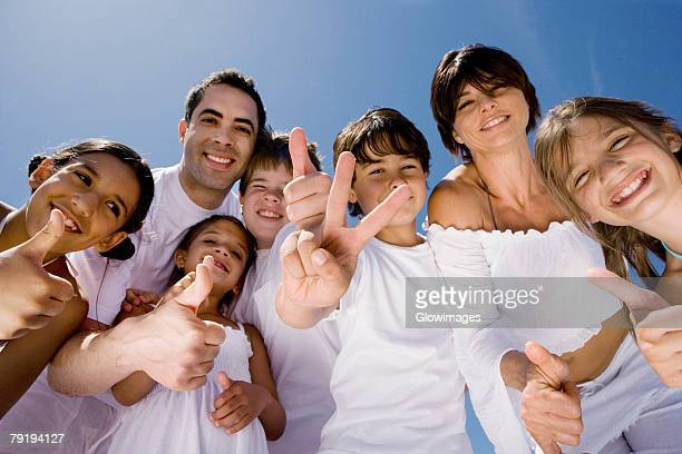 Portrait of a mid adult couple standing with five children making peace sign and thumbs up sign