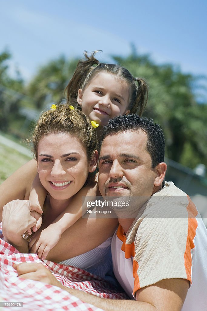 Portrait of a mid adult couple with their daughter lying on a picnic blanket : Foto de stock