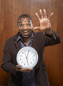 Portrait of a mid adult man carrying a clock