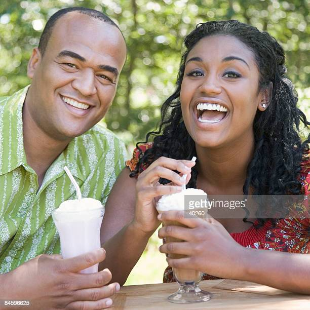 Portrait of a mid adult man drinking milkshake with a young woman