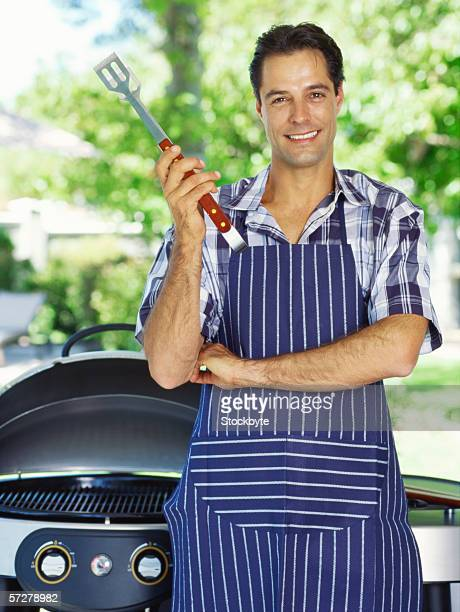 Portrait of a mid adult man holding a barbeque tongs