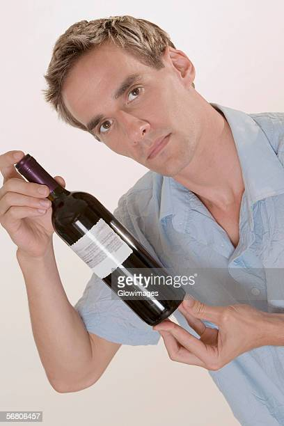 Portrait of a mid adult man holding a bottle of red wine