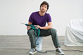 Portrait of a mid adult man holding a drill and sitting on a paint can