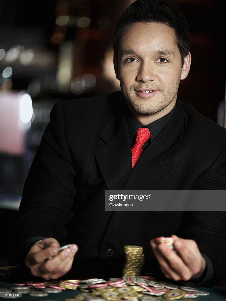 Portrait of a mid adult man holding gambling chips in a casino : Foto de stock