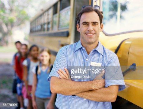 Portrait of a mid adult man near a school bus