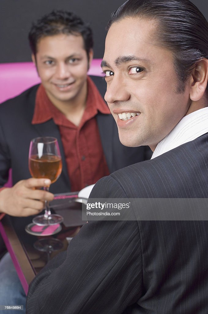 Portrait of a mid adult man sitting with a young man in a restaurant and smiling : Stock Photo