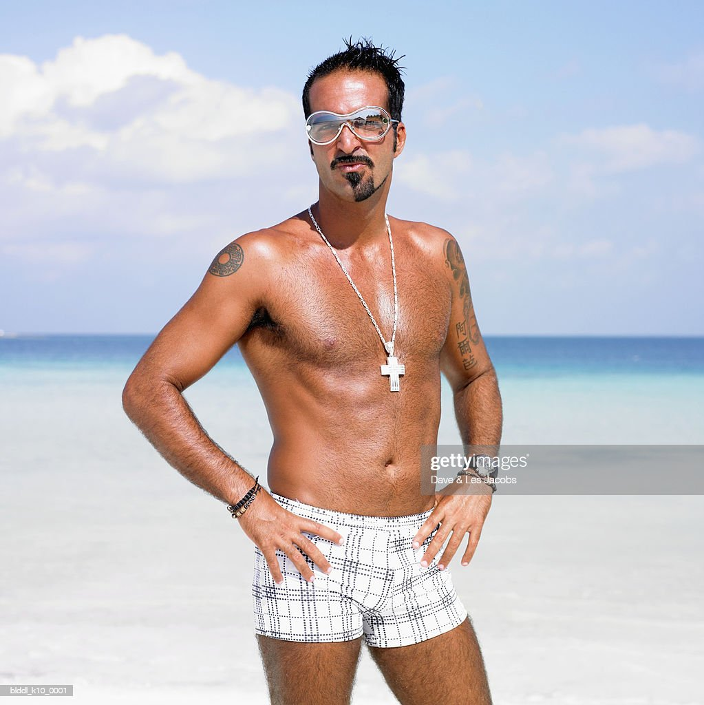 Portrait of a mid adult man standing on the beach with arms akimbo : Stock Photo