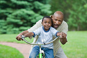 Portrait of a mid adult man teaching his son to how to ride a bicycle