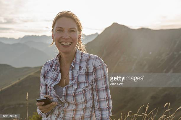 Portrait of a mid adult woman backpacker with cellphone, Achensee, Tyrol, Austria