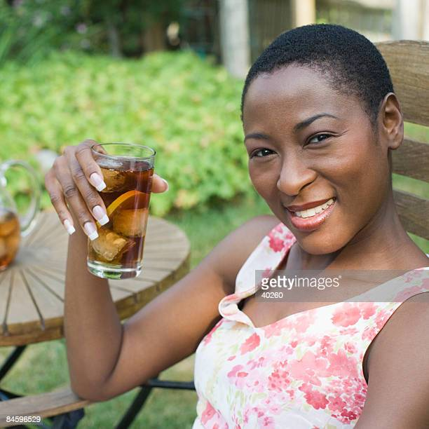 Portrait of a mid adult woman drinking ice tea and smiling