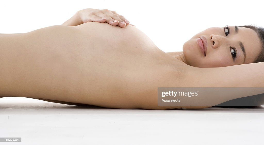 Portrait of a mid adult woman examining her breast : Stock Photo