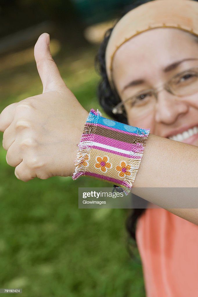 Portrait of a mid adult woman giving a thumbs up sign : Foto de stock