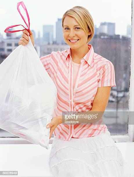 portrait of a mid adult woman holding a garbage bag
