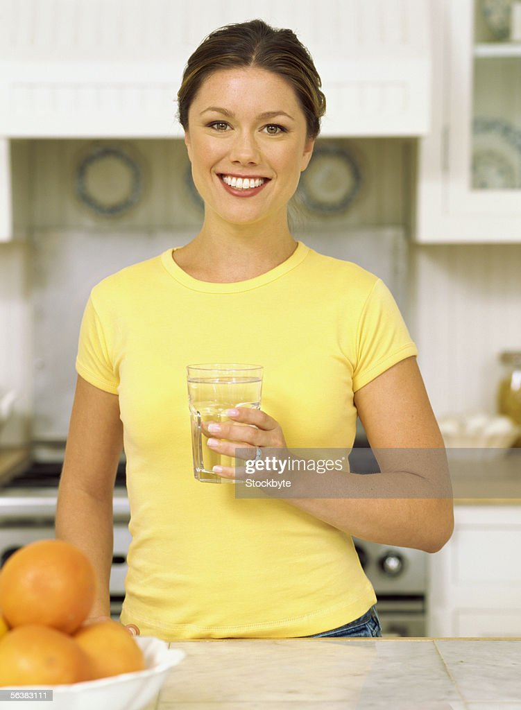 portrait of a mid adult woman holding a glass of water : Stock Photo