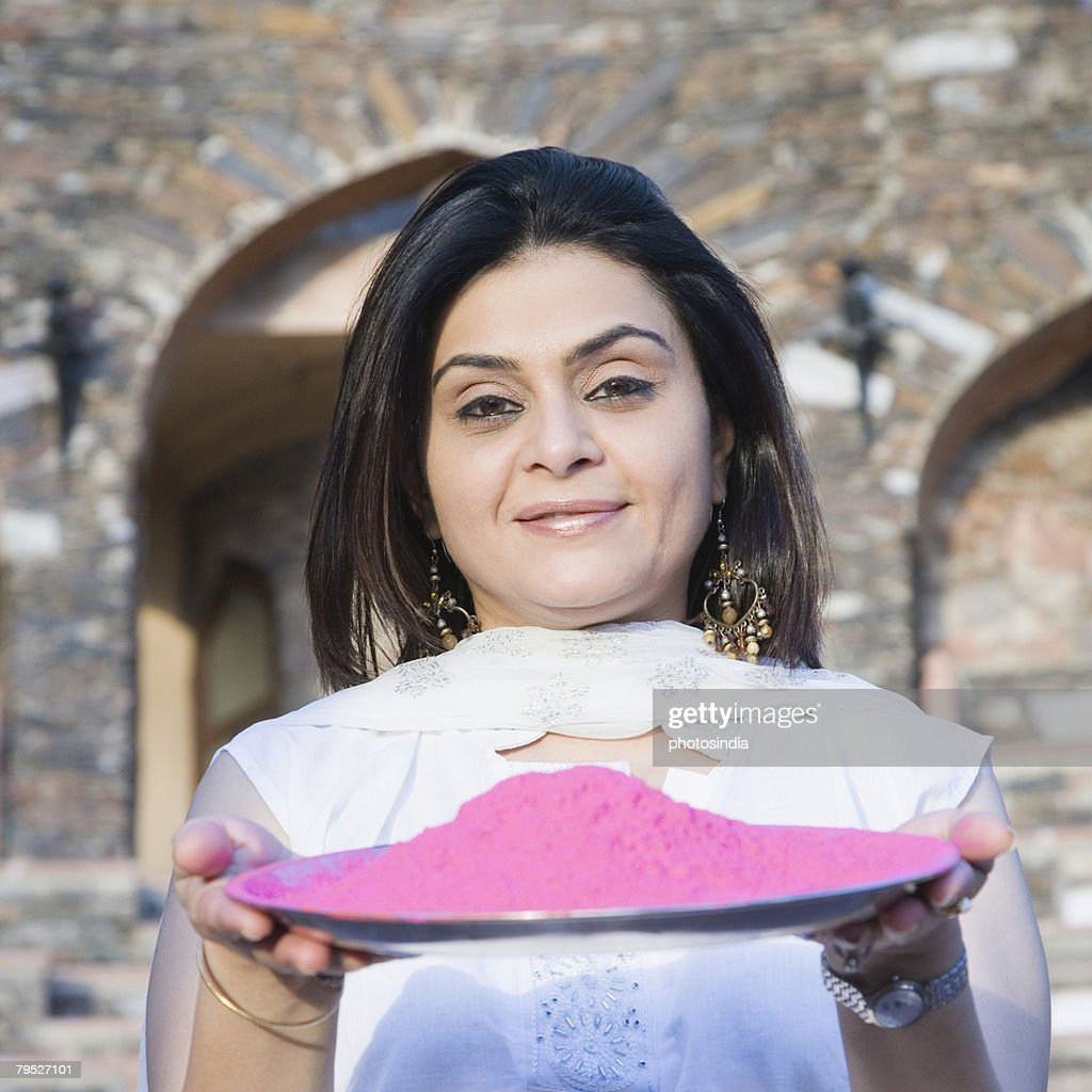 Portrait of a mid adult woman holding a plate of powder paint, Neemrana Fort Palace, Neemrana, Alwar, Rajasthan, India
