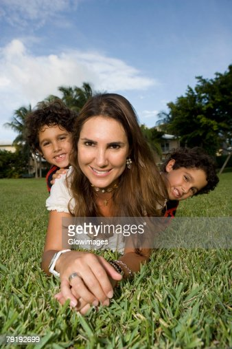 Portrait of a mid adult woman lying on grass with her two children : Foto de stock