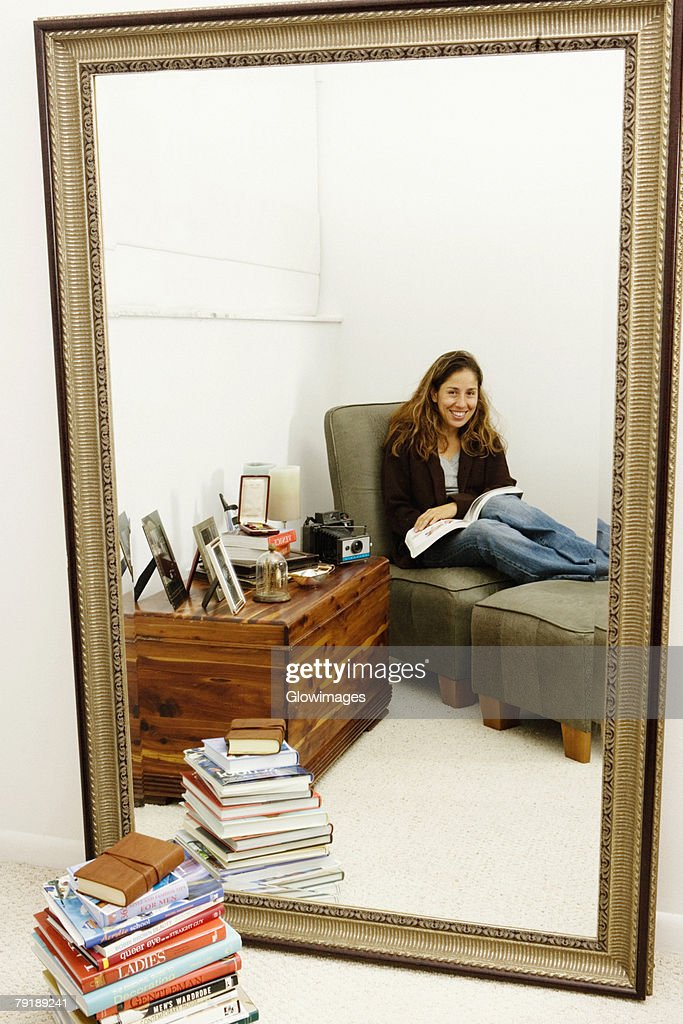Portrait of a mid adult woman sitting on a couch with a book : Foto de stock