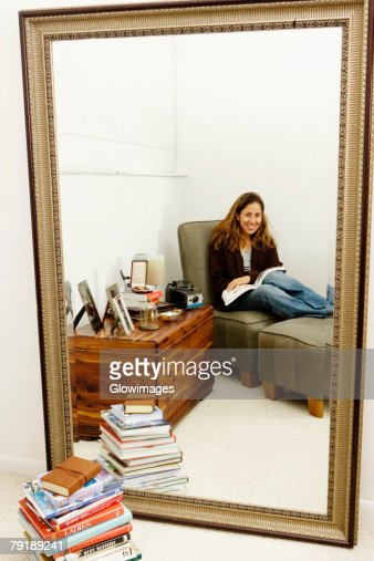 Portrait of a mid adult woman sitting on a couch with a book : Stock Photo