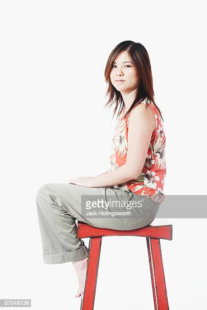 Portrait of a mid adult woman sitting on a stool