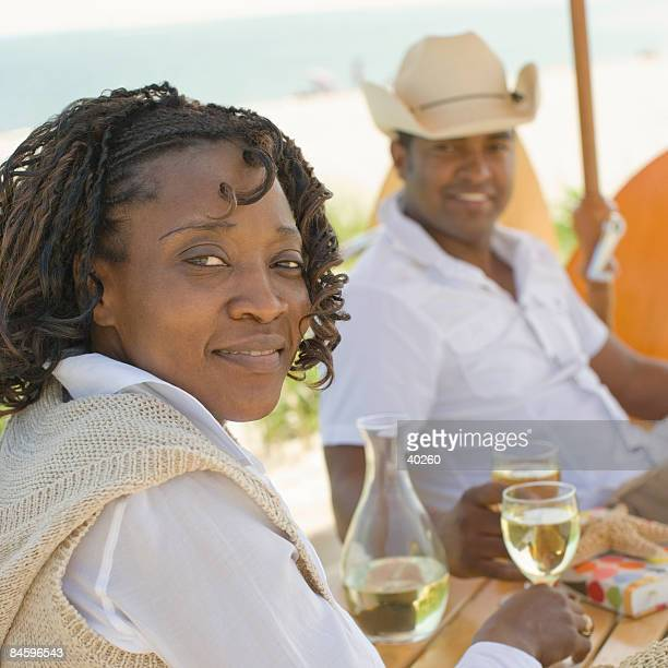 Portrait of a mid adult woman sitting on the beach with a mature man and smiling, Cape Cod, Massachusetts, USA