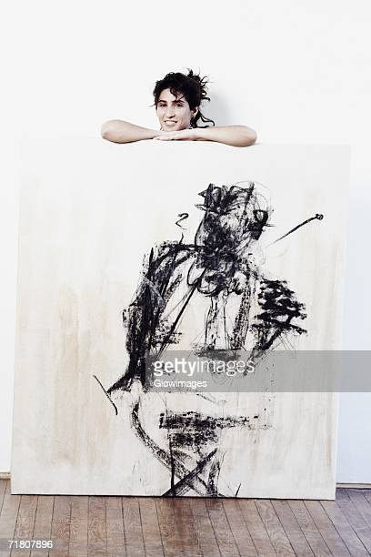 Portrait of a mid adult woman standing behind a painted wooden surface