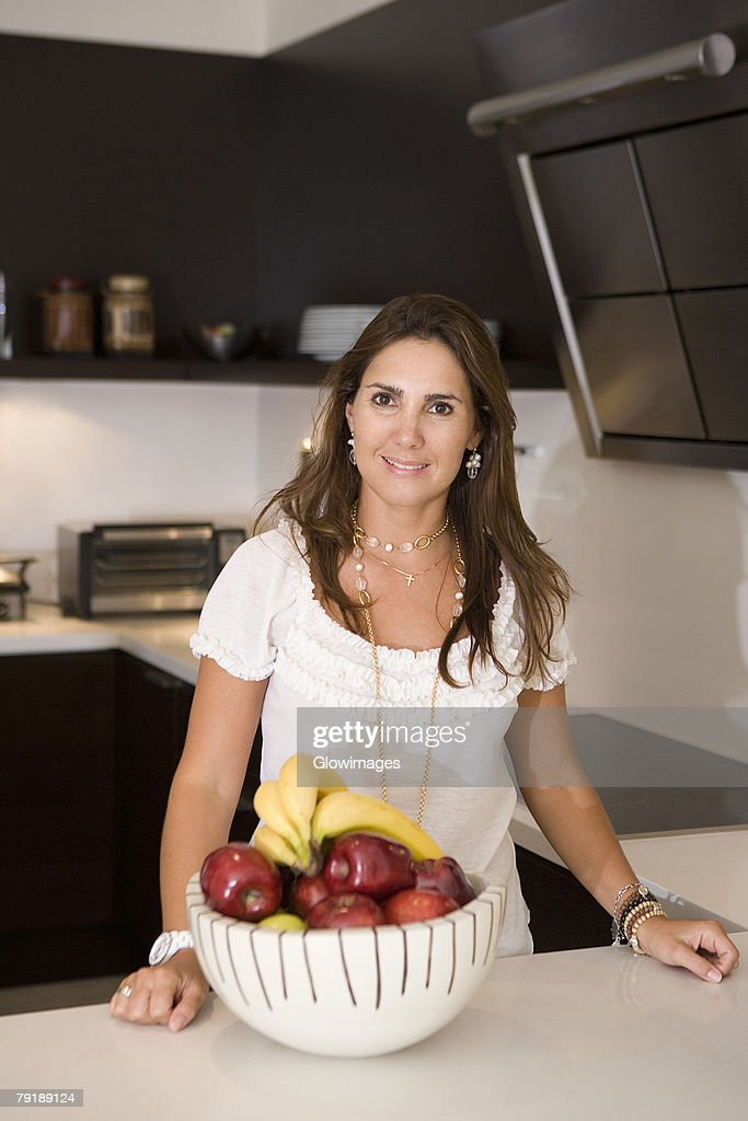 Portrait of a mid adult woman standing in front of a fruit bowl : Foto de stock