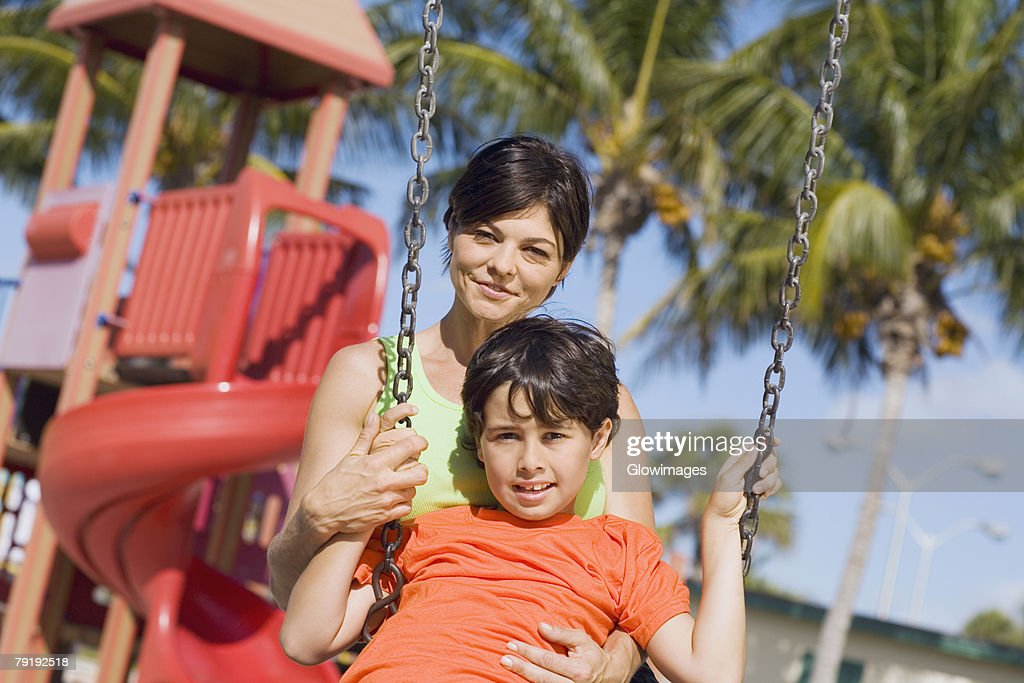 Portrait of a mid adult woman swinging on a swing with her son and smiling : Foto de stock
