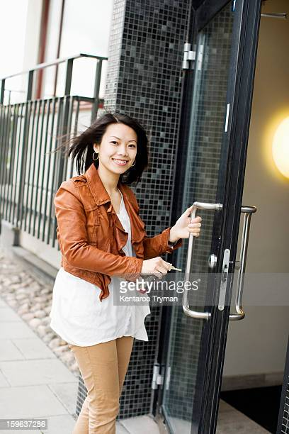 Portrait of a mid adult woman with keys entering through glass door
