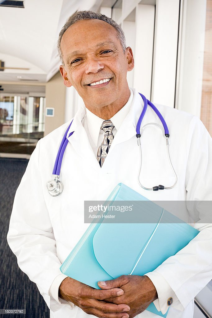 Portrait of a middle aged doctor inside a hospital : Stock Photo