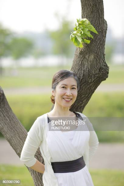 Portrait Of a middle-aged Woman Leaning On Tree Trunk