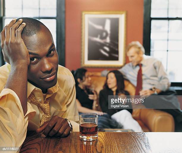 Portrait of a Miserable Businessman Leaning on a Bar Counter With Business People in the Background