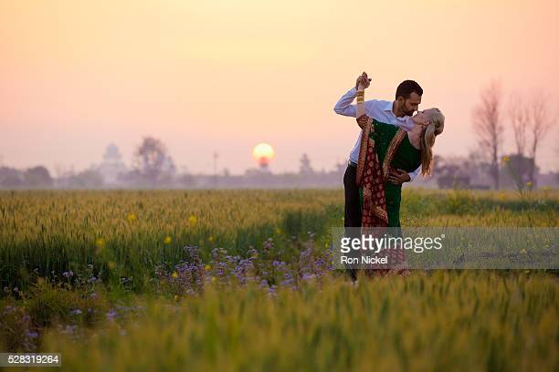 Portrait of a mixed race couple her wearing a sari in a field at sunset; ludhiana punjab india
