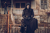 Portrait of a monk masked and dressed in black hood standing outdoors. Sect concept