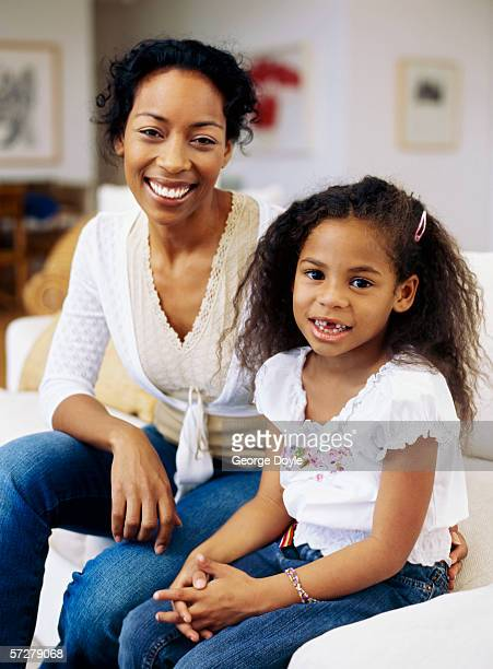 Portrait of a mother and a daughter sitting on a sofa and smiling