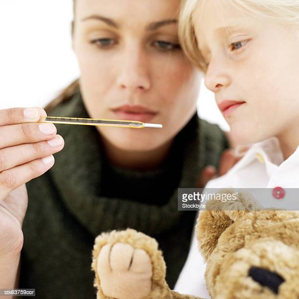 portrait of a mother and daughter reading a thermometer