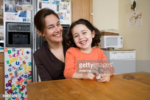 Portrait of a mother and daughter sitting at a kitchen table : Stock Photo