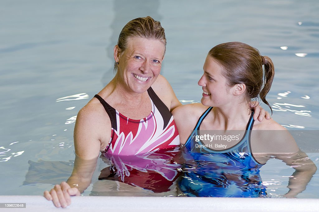 Portrait of a mother and daughter together in a swimming pool : Stock Photo