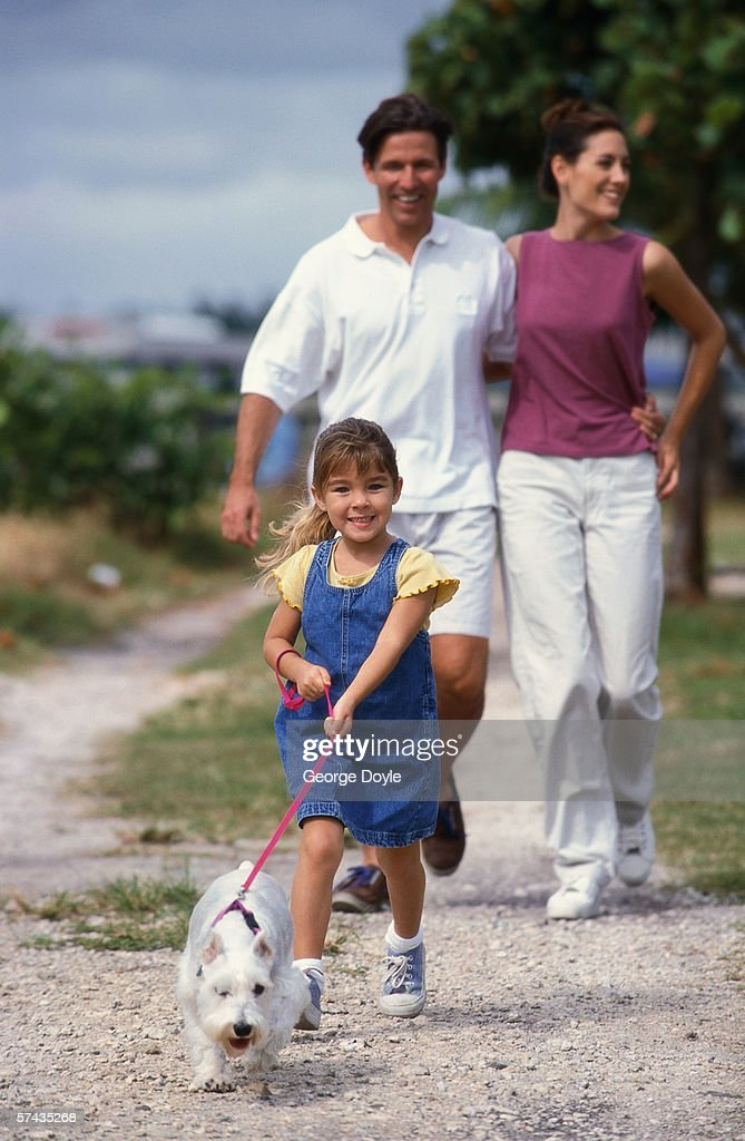 portrait of a mother and father with their daughter taking the dog for a walk : Stock Photo