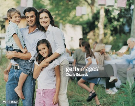 Portrait of a Mother and Father With their Son and Daughter Standing Outdoors in a Garden With their Family Sitting in the Background : Stock Photo