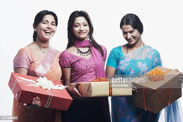 Portrait of a mother and her two daughters holding gifts