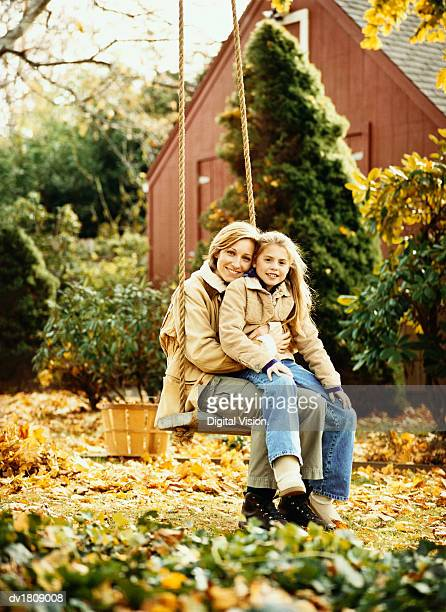 Portrait of a Mother and Her Young Daughter Sitting on a Swing in Their Garden