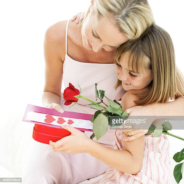 portrait of a mother hugging her daughter for a present and red rose