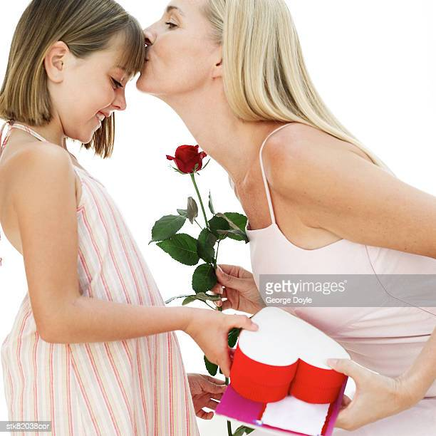 portrait of a mother kissing her daughter for a present and red rose
