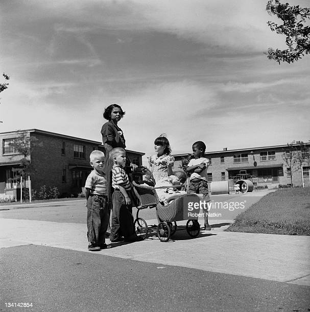 Portrait of a mother pushing a baby carriage with African American and Caucasian children gathered around her at 107th and Racine at the Racine...