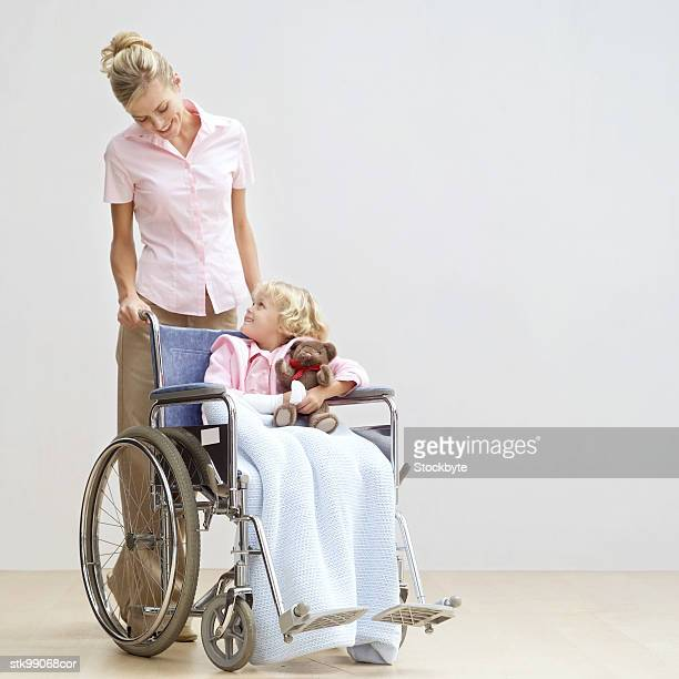 portrait of a mother pushing her daughter in a wheelchair