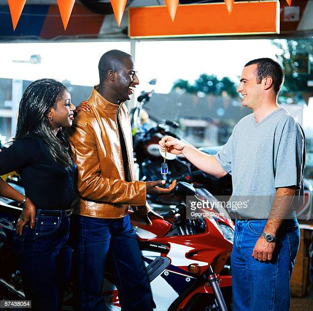 portrait of a motorcycle salesman handing over keys to a young couple