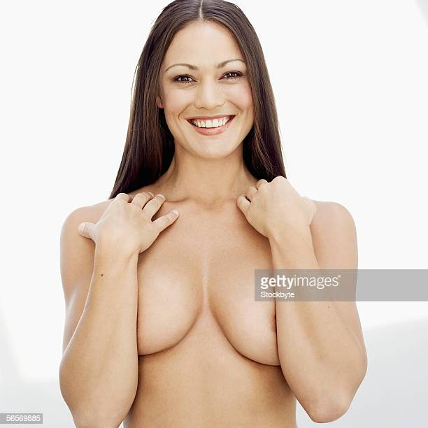 portrait of a naked young woman covering her breasts with her arms