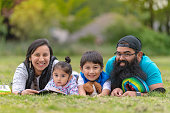 A Native American mom and dad hang out at the park and read books with their two young children on a warm summer afternoon. They're all lying in the grass and smiling at the camera.