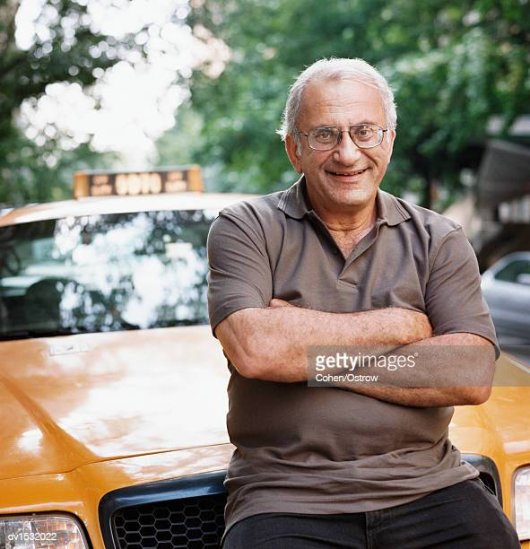 Portrait of a New York Taxi Driver Sitting on the Bonnet of His Yellow Cab