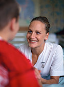 portrait of a nurse smiling and talking to a boy